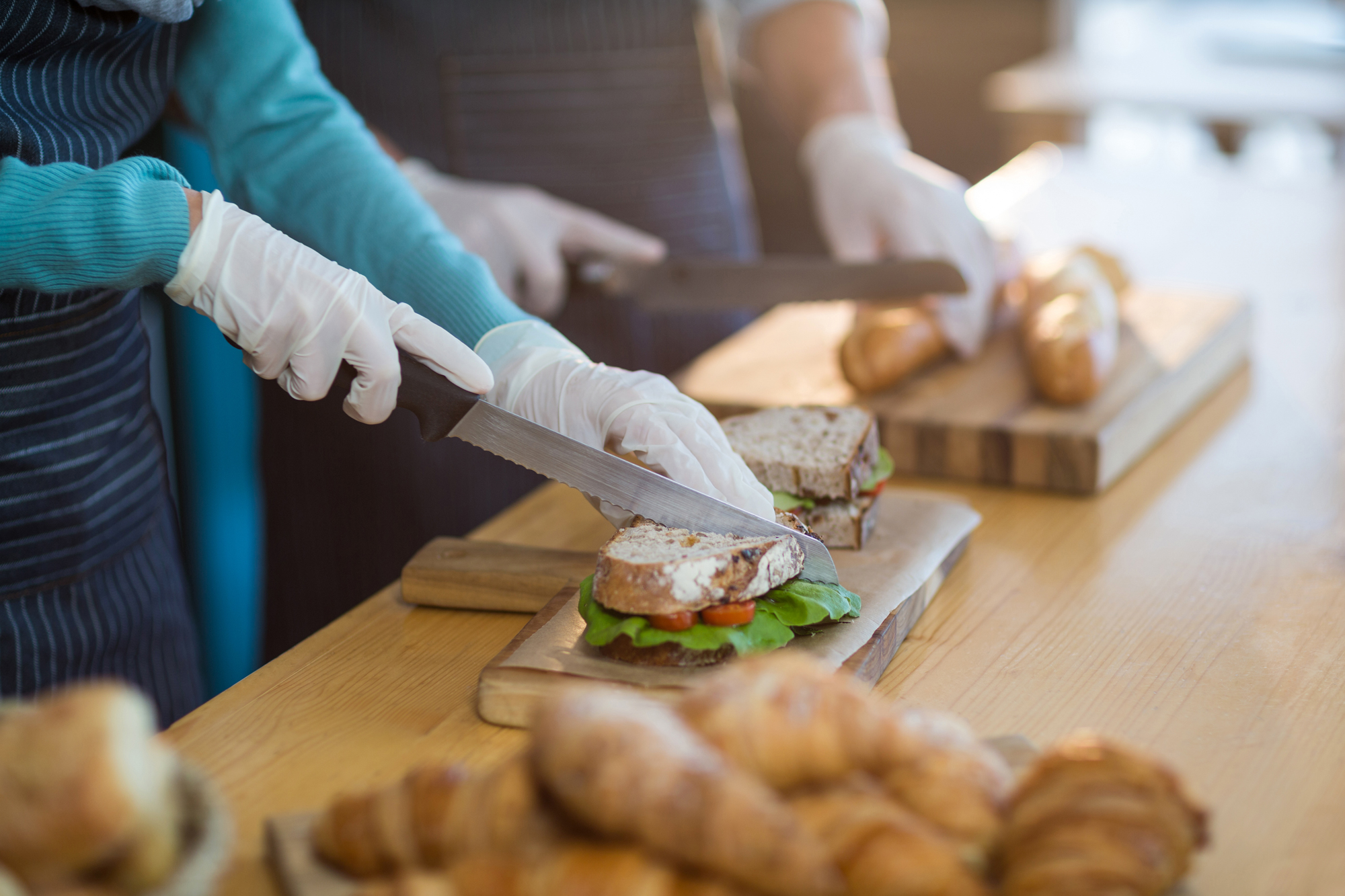 Restaurant Employee Cutting Sandwich While Wearing Gloves